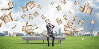 Many old books falling from above and student guy sitting on bench Royalty Free Stock Photography