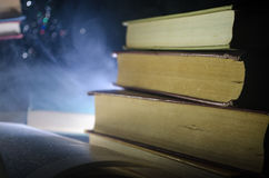 Many old books in a stack. Knoledge concept. Books on a dark background with smoke elements. Bewitched book in center Stock Photo