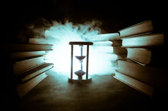 Many old books in a stack. Knoledge concept. Books on a dark background with smoke elements. Bewitched book in center Stock Photos