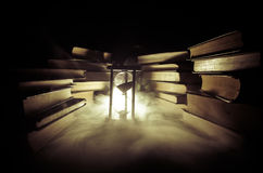 Many old books in a stack. Knoledge concept. Books on a dark background with smoke elements. Bewitched book in center Royalty Free Stock Photography