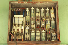 Many old electric switches on wood plate Stock Photos