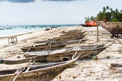 Many old fishing boats on african seashore. Many old wooden fishing boats on african seashore with ocean on the background Royalty Free Stock Images