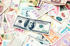 Many old money of different countries with 100 dollar bill on wo. Oden background Royalty Free Stock Images