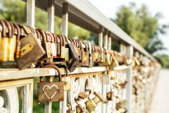 Free Many Old Rusty Metal Locks Closed On Fence Of Bridge Over River. Love Forever Through Time Concept Stock Photos - 131797413