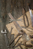 Many old rusty tools scattered on the wooden tstolu. View from above. stock image