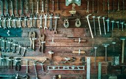 Many old tools hung on brown wood floors. Many old work tools used to be hung on brown wood floors stock image