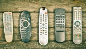 Many old TV remotes on a wooden background. Top view.  Stock Photography