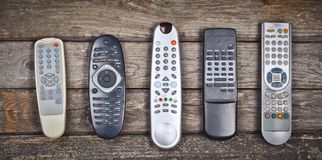 Many old TV remotes on a wooden background. Top view.  Royalty Free Stock Photo