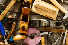 Many old working tools (axe, drill, saw and others. The old working tool. Many old working tools (axe, drill, saw and others) on a wooden background Royalty Free Stock Images