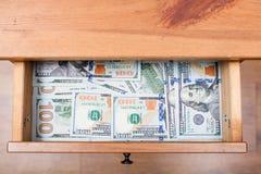 Many one hundred dollar bills on bottom of drawer Royalty Free Stock Photo