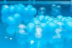 Blue balloons in water pool royalty free stock photography