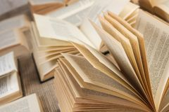 Open books on a wooden desk. Many open books on a wooden desk Stock Image