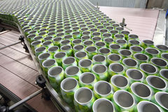 Many open green cans for drinks move on conveyor Royalty Free Stock Photography