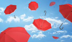 Many open red umbrellas falling from the blue sky dotted with clouds. Royalty Free Stock Photo