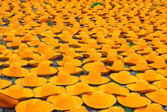 Many Orange Bamboo Farmer Hats on Ground Royalty Free Stock Image