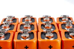 Many orange batteries, stand in several rows. Isolated on white background.  royalty free stock photo