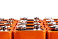 Many orange batteries, stand in several rows. Isolated on white background.  stock images