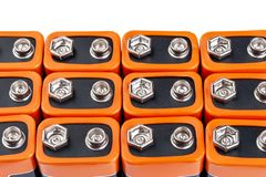 Many orange batteries, stand in several rows. Isolated on white background. Full depth of field stock photos