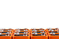 Many orange batteries, stand in several rows. Isolated on white background. Full depth of field stock image