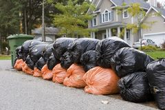 Many orange and green garbage bags at curb Stock Photo