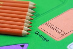 Orange pencil crayon. Many orange pencil crayons On the green color puzzle background royalty free stock photos