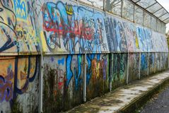 Many overlapping amateur murals. Amateur murals painted over a subway overpass with moss on royalty free stock image