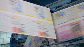 Newspaper pages on a typographical conveyor, close up. Many pages on a line