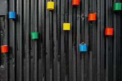 Many painted colorful empty cans reused as flower pots, mounted to the black metal wall stock photo