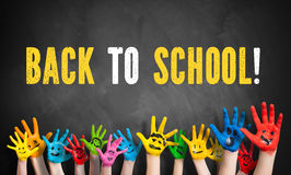 Many painted kids hands with smileys and the message `back to school!`. On a blackboard stock photos