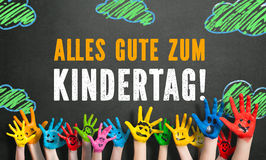 Many painted kids hands with smileys and the message `Happy Childrens Day`