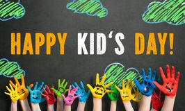 Many painted kids hands with smileys and the message `Happy Childrens Day` in German stock image