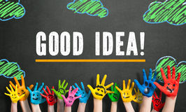 Many painted kids hands with smileys and the message 'Good Idea!' Stock Image