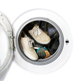 Many pairs of dirty sneakers in the washing machine. Stock Photos