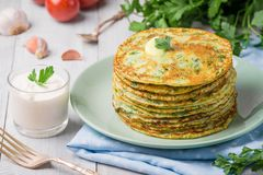 Many pancakes with fresh herbs and sour cream sauce on a wooden table. Traditional Ukrainian or Russian pancakes. Traditional dish royalty free stock images