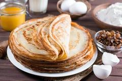 Many pancakes on a wooden background. Traditional Ukrainian or Russian pancakes. Shrovetide Maslenitsa. stock photos