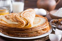 Many pancakes on a wooden background. Traditional Ukrainian or Russian pancakes. Shrovetide Maslenitsa. Traditional dishes on the holiday Carnival Maslenitsa royalty free stock image