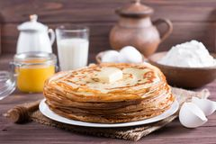 Many pancakes on a wooden background. Traditional Ukrainian or Russian pancakes. Shrovetide Maslenitsa. royalty free stock photo