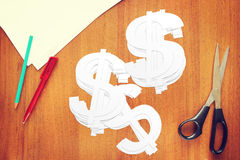 Many paper cut dollar signs on the table Stock Photo