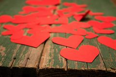 Many paper hearts on board. Photo of randomly placed red paper hearts on the old worn wooden board with green color. Hearts are near the edge of the board royalty free stock photos