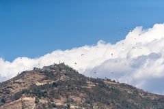 Many paragliders flyinf over the mountain Sarangkot. Royalty Free Stock Images