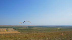 Many paragliders are flying. Silhouette people Paragliding. Paraglide flight experience skydive summer. Extreme vacation stock footage
