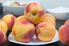 Many peaches. Many fresh peaches on plate at kitchen Stock Photo
