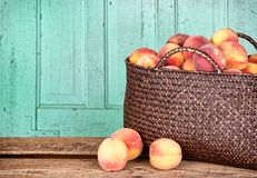 Many peaches in basket. Many peaches in a basket with antique panel background Stock Images