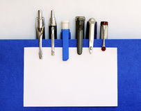 Many pens clipping the white business card. Your Text is Here stock photography