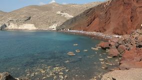 Many people came to rest and relax on closed red beach of Santorini island