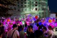 LED balloons people, holding many lighted balloons filled with toys and lights. Many people carrying LED lighted helium balloons lit by LED technology and filled royalty free stock images