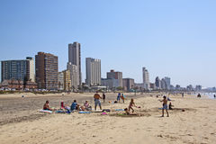 Many People and Children Enjoy a Day at the Beach. DURBAN, SOUTH AFRICA - SEPTEMBER 21, 2014: Many unknown people enjoy early morning sunshine at beach against Royalty Free Stock Images