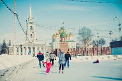 Many people in the city skating rink on the central square in the background of the Tula Kremlin. stock images