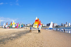Many people and colorful sail boats on beach Royalty Free Stock Images