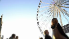 Many people coming to theme park to have fun on huge Ferris wheel, entertainment. Stock footage stock video footage